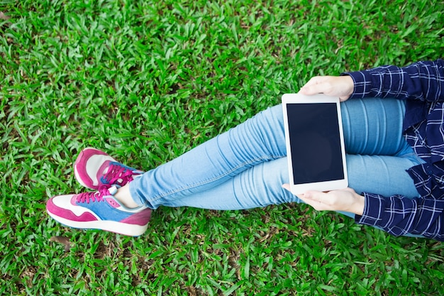 Cropped View of Girl Using Tablet on Grass Free Photo
