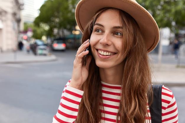 優しい笑顔で幸せなコーカイザン女性のトリミングされたビュー、携帯電話で話し、脇を見る 無料写真