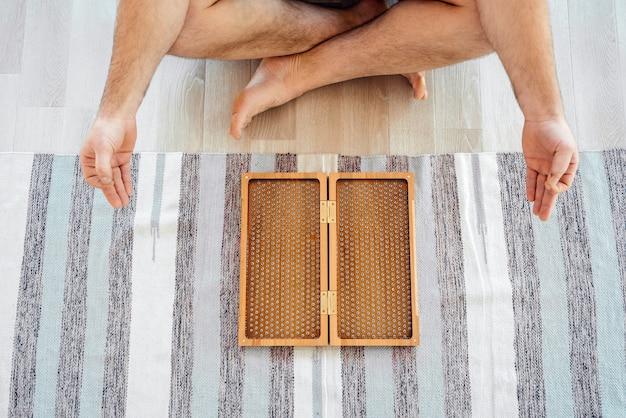 Обрезанный вид человека, занимающегося йогой, медитации и сидящего на полу возле доски садху Premium Фотографии
