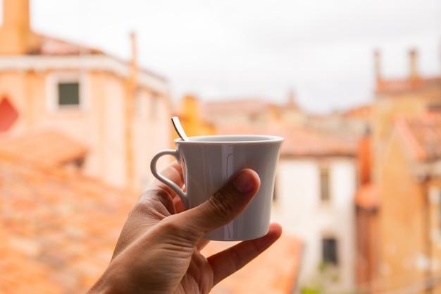イタリア、ベニスの背景に都市の景観とコーヒーを抱きかかえたのトリミングビュー。 Premium写真
