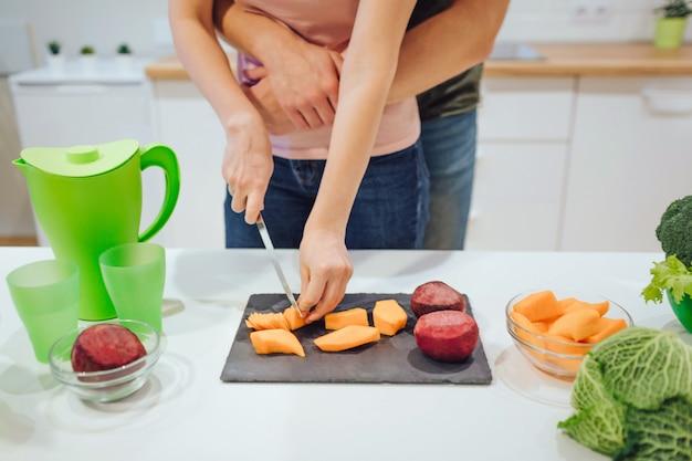 Подрезанный взгляд рук женщины режа органические овощи. веганские любящая семья готовит овощи на кухне. Premium Фотографии