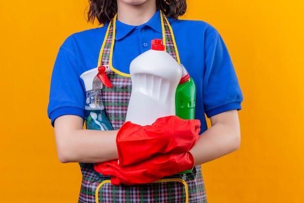 Обрезанный вид женщины в фартуке и резиновых перчатках, держащей пространство для чистящих средств Бесплатные Фотографии