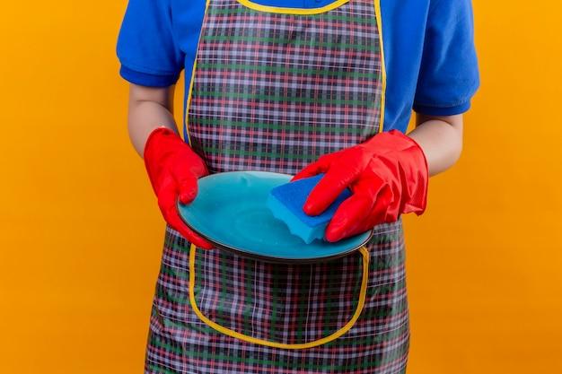 皿を洗う手で食器を保持しているエプロンとゴム手袋を着用している女性のトリミングビュー 無料写真