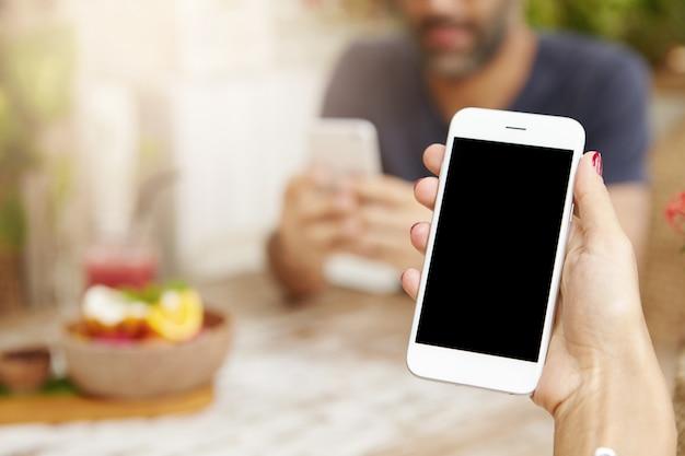 카페에서 점심 시간 동안 터치 스크린 스마트 폰을 사용하는 젊은 여성의 자른보기 무료 사진