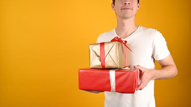 Обрезанный вид молодого красавца, держащего подарочные коробки на желтом Premium Фотографии