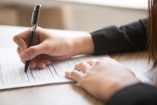 Cropped view of woman filling in application form Free Photo