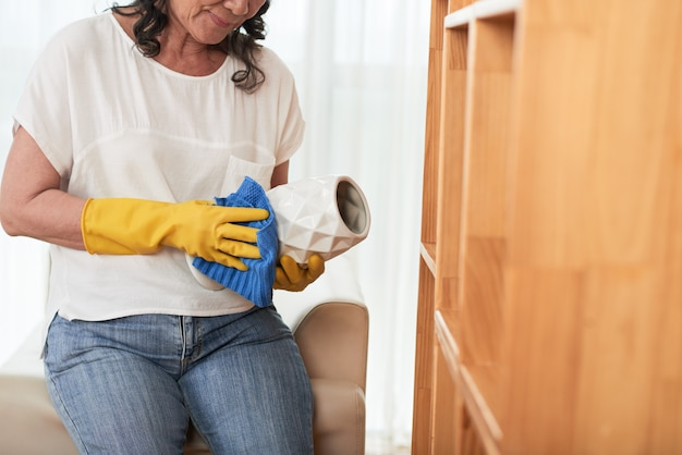 Cropped woman cleaning vase with a cloth Free Photo