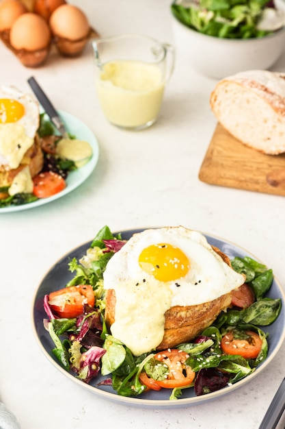 Croque madame with ham, melted emmental, fried egg and bechamel. Premium Photo