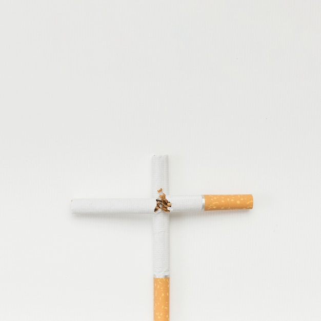 Cross sign made from broken cigarette over white background Free Photo