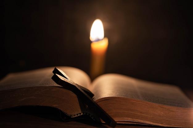 古いオークの木製テーブルの上の聖書とキャンドルを渡ります。 無料写真