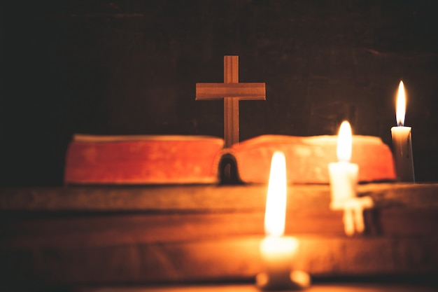 Cross with bible and candle on a old oak wooden table. beautiful gold background. Free Photo
