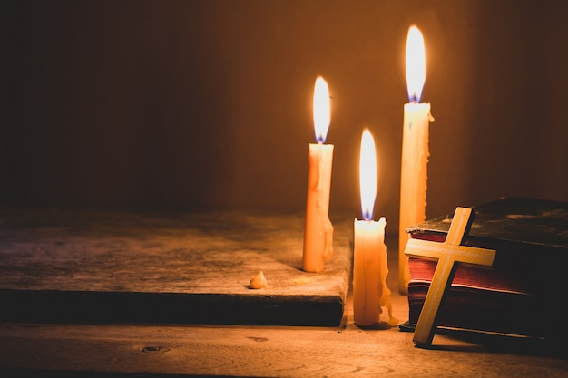 Cross with bible and candle on a old oak wooden table. beautiful gold background. Premium Photo