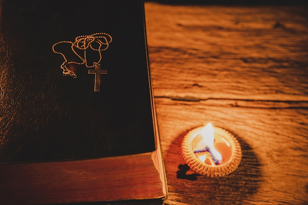 Cross with holy bible and candle on a old oak wooden table. Free Photo