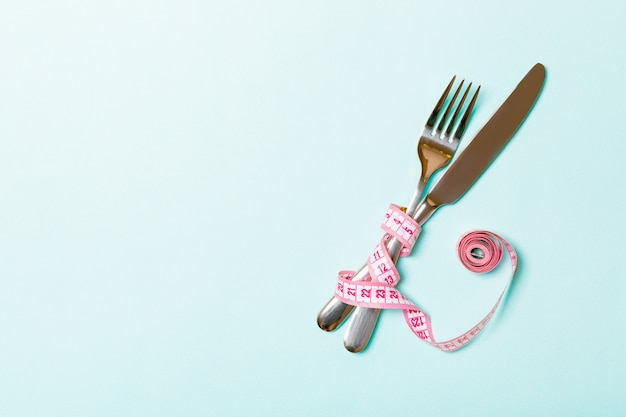 Crossed fork and knife are wrapped in measuring tape Premium Photo