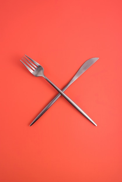 Crossed forks and a knife on an orange background, a symbol of catering, cafe, restaurant. Premium Photo