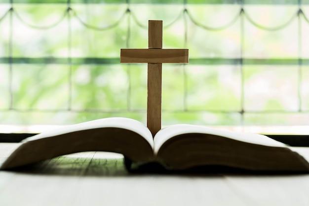 나무 테이블에 성경 위에 열리는 십자가 무료 사진