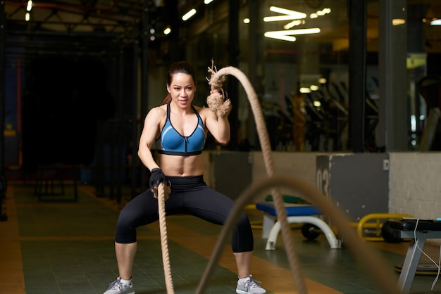 Crossfit exercise performed by a strong woman with rope Free Photo