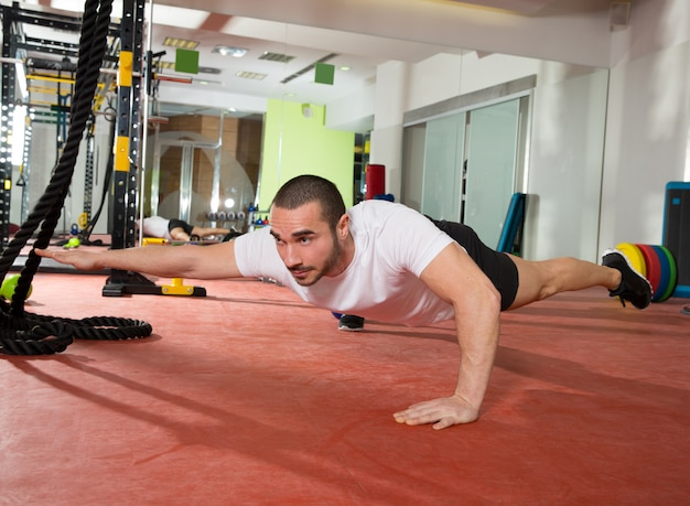 Crossfit fitness man balance pus ups with one leg and arm Premium Photo