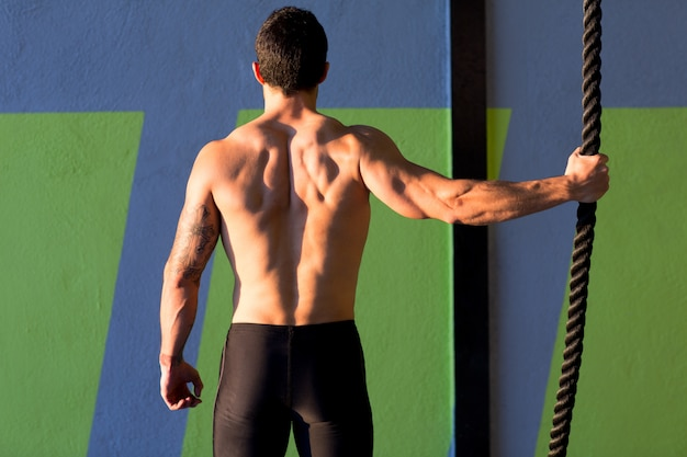 Crossfit gym man holding hand a climbing rope Premium Photo