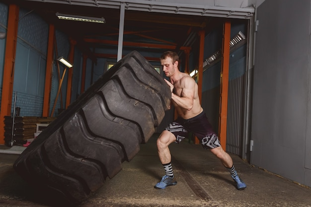 Crossfit sport training concept - man flipping tire. Premium Photo