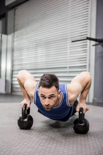 Crossfitジムでケトルベルで腕立て伏せ筋肉男 Premium写真