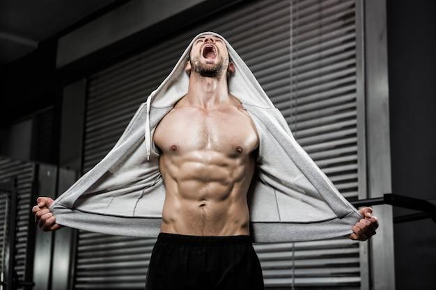 Crossfitジムで叫んで灰色のジャンパーと上半身裸の男 Premium写真