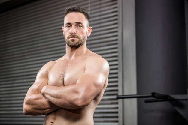 腕を組んでcrossfitジムで立っている上半身裸の男の肖像 Premium写真