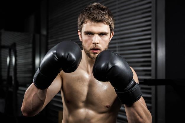 Crossfitジムでボクシンググローブを持つ上半身裸の男 Premium写真