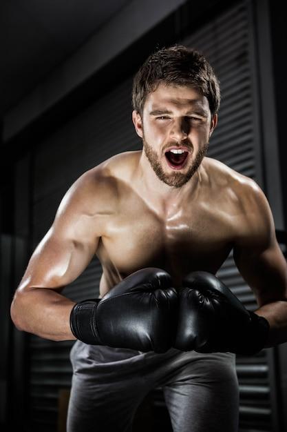 Crossfitジムで叫んでボクシンググローブを持つ上半身裸の男 Premium写真
