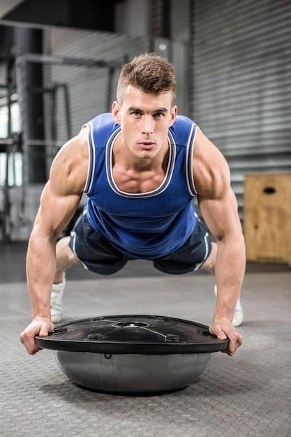 Crossfitジムでボスボールをプッシュアップしている筋肉男 Premium写真