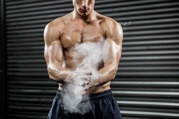 上半身裸の男がcrossfitジムでタルクで手をたたく Premium写真