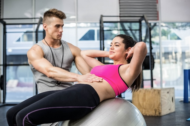 Crossfitジムで腹筋を持つ女性を支援する男性のトレーナー Premium写真