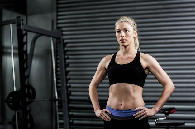 Crossfitジムで腰に手を持つ女性に合う Premium写真
