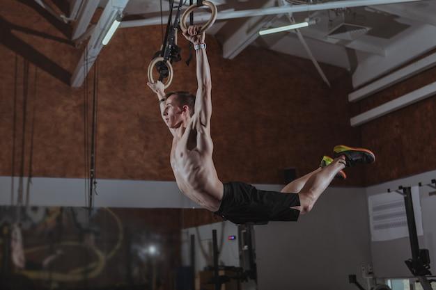 体操リングでワークアウト筋肉男性crossfitアスリート Premium写真