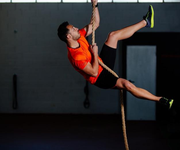 ジムでロープを登るcrossfitアスリート男 Premium写真