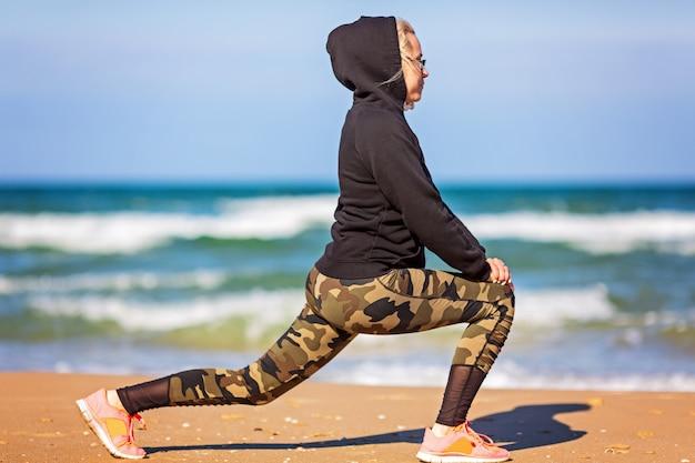 トレーニングコンセプトcrossfitフィットネストレーニングスポーツとライフスタイル。パーカーの女性、レギンス。健康とスポーツのコンセプトです。アウトドアスポーツ活動 Premium写真
