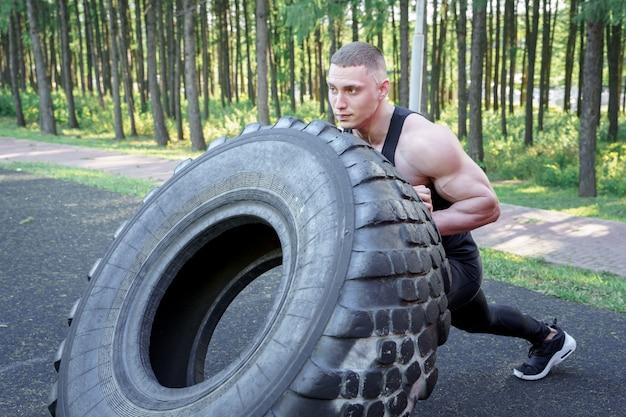屋外で運動しながらタイヤを弾く強い若い男。 crossfit。 Premium写真