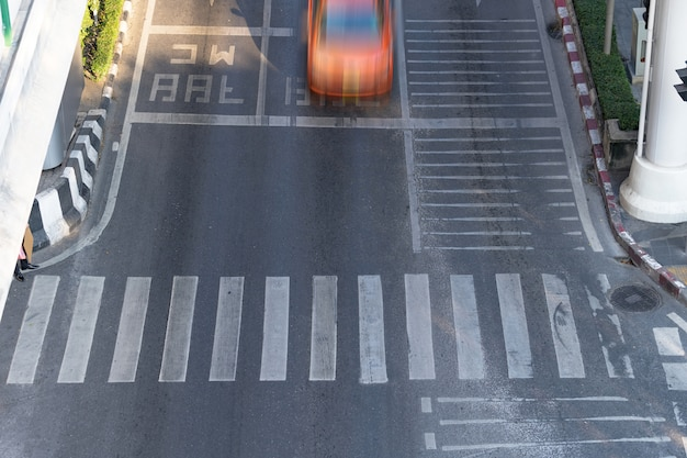 Crosswalk and car, busy city street and car in motion blur on crosswalk Premium Photo