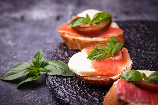 Crostini with salmon, mozarella, tomato and basil. italian starter or appetizer Premium Photo