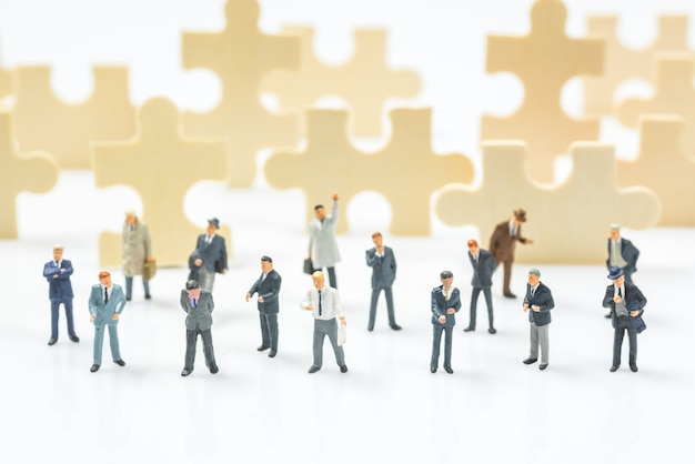 Crowd Of Business Miniature People On Jigsaw Puzzle Piece Field