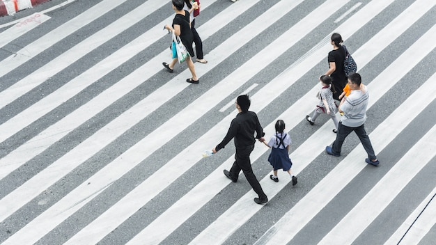 Crowd of people and group of family with child walk on street pedestrian crossroad in the city street Premium Photo