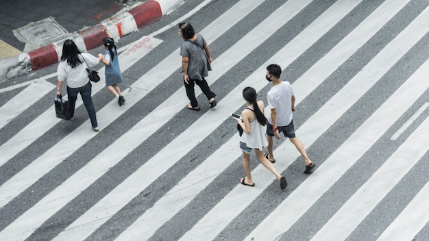 Crowd of people and group of family with child walk on street pedestrian crossroad in the city street. Premium Photo