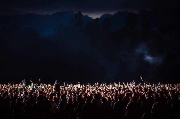 Crowd of spectators at a concert at night lit by a spotlight from the stage Premium Photo