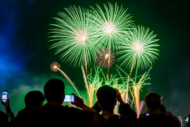 Crowd watching fireworks and celebrating city founded.green tone light. Premium Photo