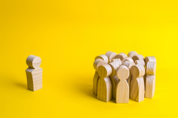 The crowd of wooden figures of people stand distantly and look at the red man. bad busines Premium Photo