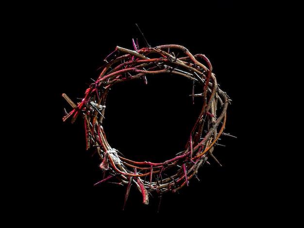 暗闇の中で光の赤い色合いのいばらの冠。聖週間の概念、イエスの苦しみとはりつけ。 Premium写真