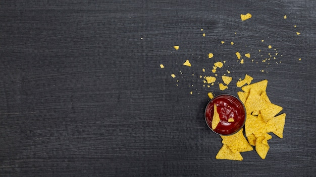 Crumbled traditional nachos with tomato dip Free Photo