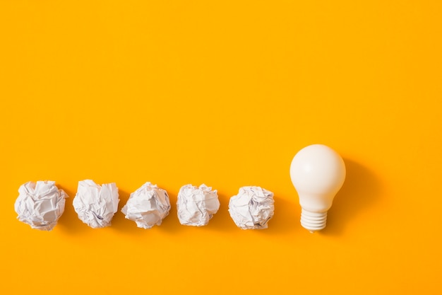 Crumpled paper ball with white light bulb on yellow background Free Photo