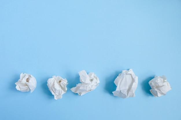 Crumpled paper balls on blue. concept idea and creative Premium Photo