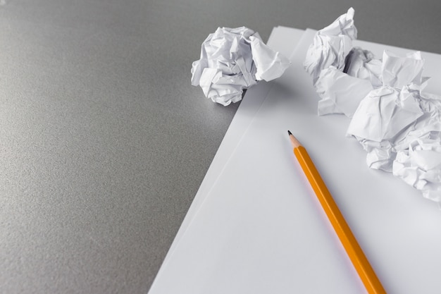 Crumpled paper balls and a pencil with empty paper shit Premium Photo